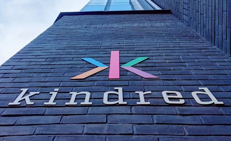 Kindred Groups logotyp på väggen i byggnaden